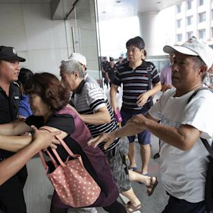 Relatives of passengers who were onboard Malaysia Airlines flight MH370 push policemen as they try to enter building where office of Malaysia Airlines is located in Beijing