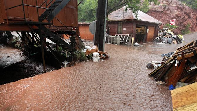 In this Aug. 12, 2013, photo, earth-filled water from a heavy rainstorm begins to flow over a drainage creek during flooding which occurred three days after a deadly flash flood struck at the same location, causing millions of dollars in damage, in Manitou Springs, Colo. Manitou Springs lies downstream of the vast swaths of scorched earth left behind by last year's Waldo Canyon Fire, making the town highly prone to flash flooding. In Colorado, multiple flash floods have struck this summer in or near scars left by last year's wildfires. (AP Photo/Brennan Linsley)