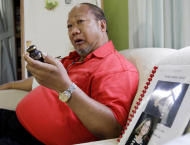 In this photo taken Aug. 4, 2011 at his home in Tagaytay City, south of Manila, Philippines, Rudy Abad, sitting beside the picture of his late wife Marie Rose Abad, holds a small urn in which he keeps a portion of his wife's ashes who died during the Sept. 11 2001 World Trade Center terrorist attacks in New York City. Unlike many victims of the 2001 attacks who are remembered mostly by their family and friends, Marie Rose Abad's legacy lives on half-way around the world in a once-notorious Manila slum now turned into a tidy village that carries her name. (AP Photo/Pat Roque)