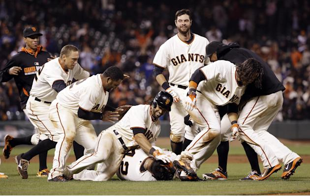 San Francisco Giants' Hector Sanchez, bottom center, is mobbed by teammates after driving in the game-winning run during the 12th inning of a baseball game against the Los Angeles Dodgers on Wedne