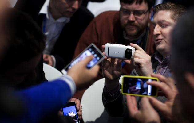 Visitors and industry experts compare phones at last year's Mobile World Congress (PA)