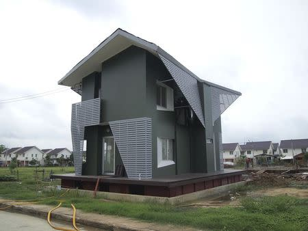 In this picture provided by Site-Specific Co Ltd, the 2.8 million baht ($86,000) amphibious house, designed and built by the architecture firm Site-Specific Co Ltd for Thailand's National Housing Authority (NHA) rises up 85cm after architects and NHA staff fill a manmade test hole underneath the house with water during a trial run in Ban Sang village of Ayutthaya province September 7, 2013. REUTERS/Site-Specific Co Ltd/Handout via Reuters