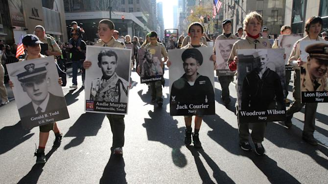 Pictures of WWII veterans are carried up New York's Fifth Avenue during the Veterans Day Parade Sunday Nov. 11, 2012. (AP Photo/Tina Fineberg)