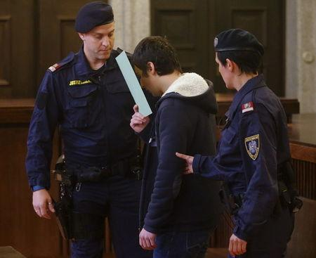 A 14-year-old terror suspect is led into court by prison guards in St. Poelten