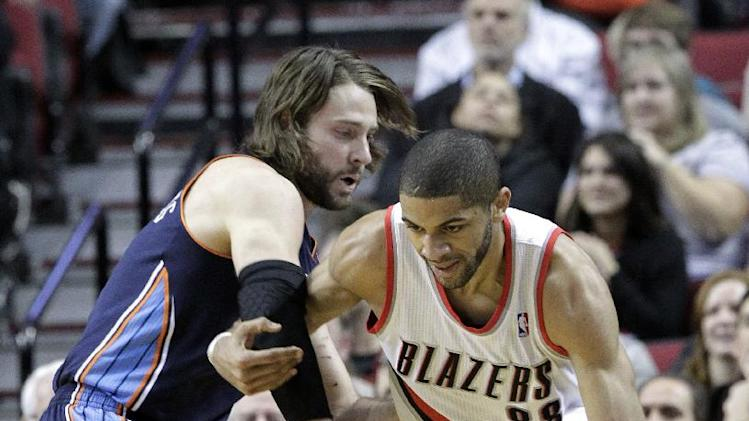 Portland Trail Blazers forward Nicolas Batum, right, from France, drives on Charlotte Bobcats forward Josh McRoberts during the first half of an NBA basketball game in Portland, Ore., Thursday, Jan. 2, 2014. (AP Photo/Don Ryan)