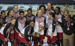The United States basketball players and coach Geno Auriemma, right, pose with their trophy and gold medals following their victory over Spain in Basketball Championship for Women's final at Fenerbahce Arena in Istanbul, Turkey, Sunday, Oct. 5, 2014. Maya Moore scored 18 points and the U.S. beat Spain 77-64 to win its second straight gold medal in the championship. (AP Photo/Emrah Gurel)