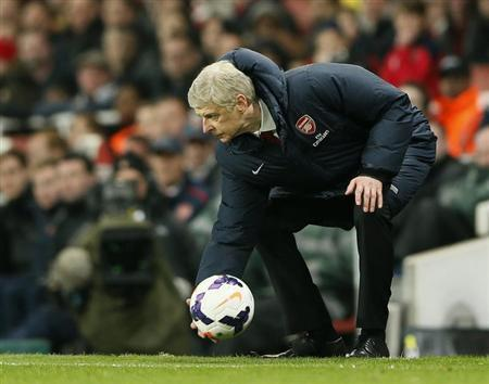 Arsenal manager Arsene Wenger picks up the ball during their English Premier League soccer match against Swansea City at the Emirates stadium in London