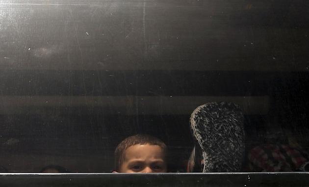 A Palestinian boy sitting a bus looks out a window as he returns to Gaza at the Rafah border crossing between Egypt and southern Gaza Stri