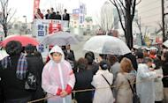 People listen to an election campaign speech by Prime Minister Yoshihiko Noda (background C) of the ruling Democratic Party of Japan, a day before lower house election, in Tokyo, on December 15, 2012. Voters in Japan go to the polls on Sunday in an election likely to return long-ruling conservatives to power after three years in the wilderness.