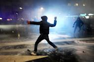 A demonstrator throws a rock to riot police during clashes on the sidelines of a protest against the government in downtown Sofia on February 19, 2013. Bulgaria's prime minister announced Wednesday the surprise resignation of his government after days of sometimes violent rallies, paving the way for early elections in the European Union's poorest member