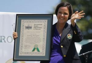 Former tennis player Lindsay Davenport of the United States waves and holds her plaque after being inducted into the International Tennis Hall of Fame in Newport