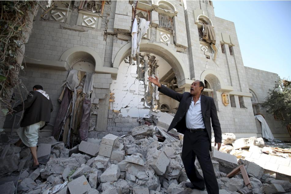 A man screams in front of the residence of Yemen's former President Ali Abdullah Saleh after airstrikes hit it in Sanaa