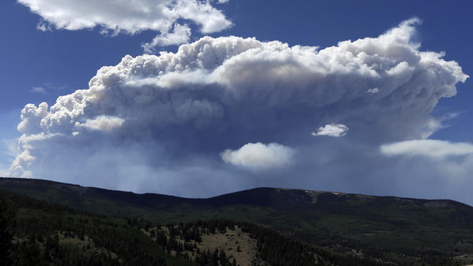 Wildfire smoke plumes above Del Norte Peak on Sunday, June 23, 2013, in near Del Norte, Colo. A large wildfire near a popular summer retreat in southern Colorado continues to be driven by winds and fueled by dead trees in a drought-stricken area, authorities said Sunday. (AP Photo/Gregory Bull)