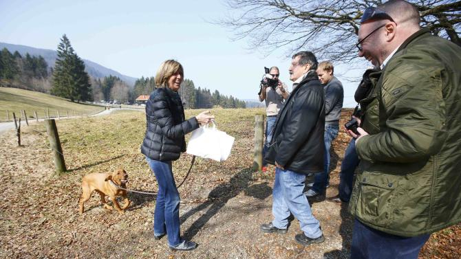 A woman from a local beer garden brings sausages in buns on behalf of Hoeness, resigned president and chairman of Bayern Munich, to journalists standing on public ground near his house in the Bavarian town of Bad Wiessee