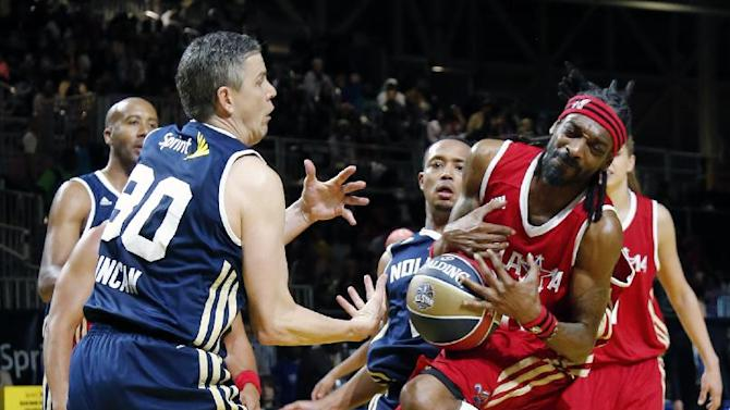 U.S. Education Secretary Arne Duncan, left of the East team struggles with West's Snoop Dogg for a loose ball in the second half of the NBA All-Star Celebrity basketball game in New Orleans, Friday, Feb. 14, 2014. The East won 60-56