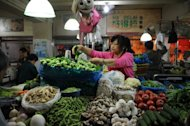 A vendor sells vegetables in a market in Shanghai. Food prices, which account for nearly one-third of China's CPI, rose 3.0% in November year-on-year, the National Bureau of Statistics said