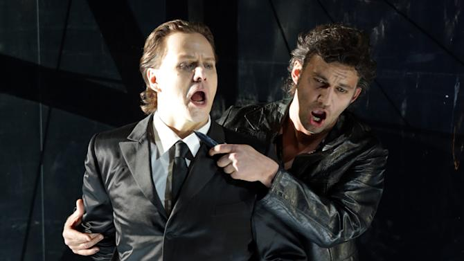 "In this picture taken Friday, June 21, 2013, Jonas Kaufmann, right, in the role of Manrico and Alexey Markov as Earl of Luna sing during a dress rehearsal for the opera ""Il Trovatore"" by Giuseppe Verdi in the Bavarian State Opera House in Munich, southern Germany. This wild new production by Olivier Py opened the company's annual Munich Opera Festival. It's a non-stop barrage of nightmarish images mixing styles and periods that assault the audience at lightning speed on a multi-tiered revolving set. (AP Photo/Matthias Schrader)"
