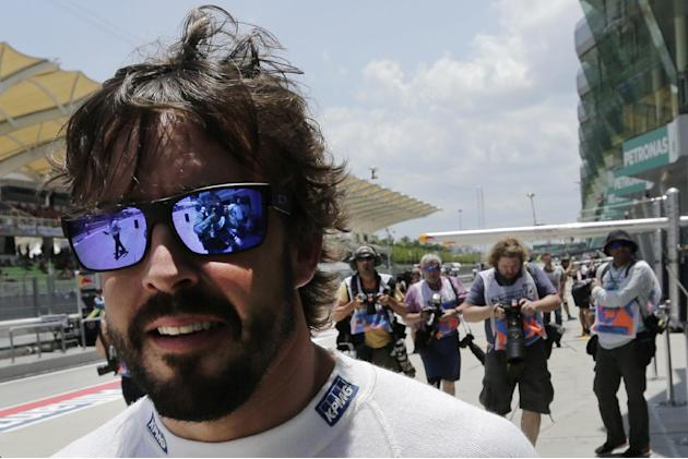 McLaren driver Fernando Alonso of Spain walks along the pit lane before the second practice session for the Malaysian Formula One Grand Prix at Sepang International Circuit in Sepang, Malaysia Friday,