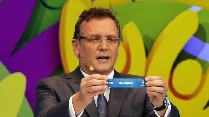 "FIFA Secretary General Jerome Valcke holds the slip showing ""Colombia"" during the draw for the 2014 World Cup at the Costa do Sauipe resort in Sao Joao da Mata"