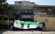 "A picture released by the Syrian opposition's Shaam News Network shows rebels celebrating with a pre-Baath Syrian flag after taking over a police station in Aleppo. UN chief Ban Ki-moon told world powers they must overcome their rivalries to put an end to the ""proxy war"" in Syria, as deadly fighting raged in Damascus and the country's second city Aleppo"