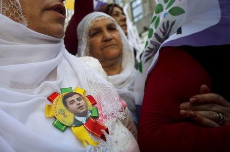 Supporter of pro-Kurdish Peoples' Democratic Party (HDP) wears a lapel pin with a picture of HDP co-leader Selahattin Demirtas during a protest against attacks on their party offices, in central I