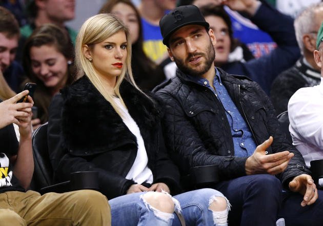 Boston Bruins' Patrice Bergeron and his wife Stephanie look on from court side during the second quarter of an NBA basketball game between the Boston Celtics and the Golden State Warriors in Bosto
