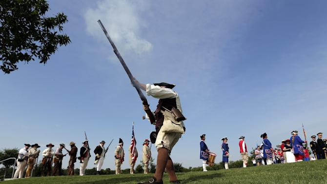 "Ed Lunderman, a member of a Living History Musket Detail, fires his musket to represent ""the Shot Heard Around the World"" during a Fourth of July Patriotic Ceremony at Fort Sam Houston National Cemetery, Thursday, July 4, 2013, in San Antonio. (AP Photo/Eric Gay)"