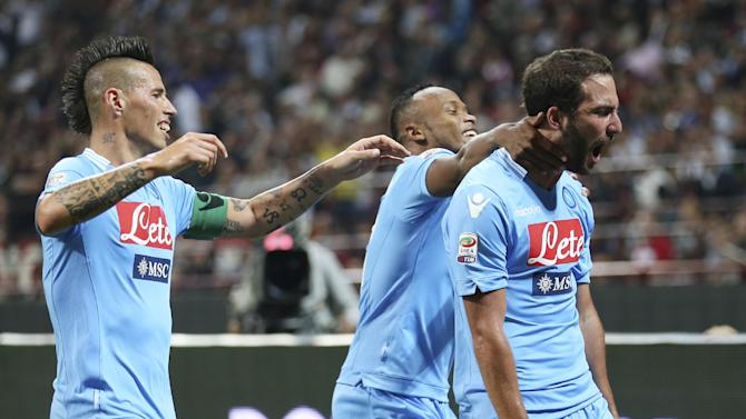 Napoli forward Gonzalo Higuain, right, of Argentina, celebrates with his teammates Marek Hamsik, left, and Camilo Zuniga, of Colombia, after scoring during the Serie A soccer match between AC Milan and Napoli at the San Siro stadium in Milan, Italy, Sunday, Sept. 22, 2013