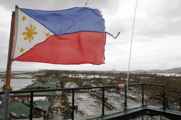 A Philippine flag flutters atop the control tower of a damaged airport after super Typhoon Haiyan battered Tacloban city