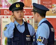 Policemen patrol at a Tokyo railway station on June 9. A pair of skeletons have been found in a car at the bottom of a reservoir in Japan, 17 years after two brothers disappeared while out for a drive in the area, police said Tuesday