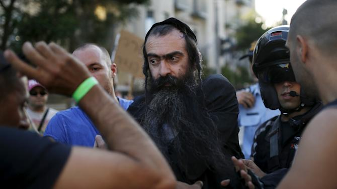 People detain after disarming an Orthodox Jewish assailant, after he stabbed and injured six participants of an annual gay pride parade in Jerusalem on Thursday, police and witnesses said