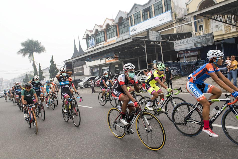 Cyclists wear mask as they compete during haze affected 6th stage of Tour de Singkarak in Bukit Tinggi