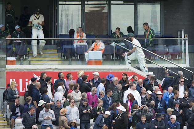Australia's Mitchell Johnson, centre right wearing white, makes his way back to the dressing room after being caught on 3 by Ben Stokes off the bowling of England's James Anderson on the first
