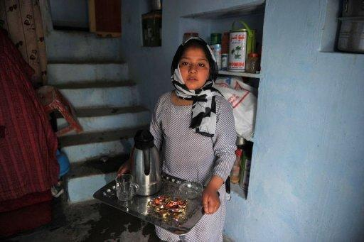 Eleven year old Afghan girl Tarana Akbari carries a tray of tea after an interview with an AFP reporter at her home