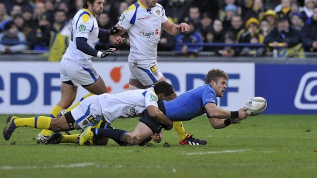 Leinster's Irish fullback Ian Madigan (R) tries to pass the ball despite Clermont's players during their European Cup rugby union match ASM Clermont-Auvergne vs Leinster rugby on December 9, 2012