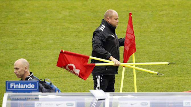 Finland's soccer head coach Mixu Paatelainen carries flags during a training session at the Stade de France stadium in Saint Denis, north of Paris, Monday, Oct. 14, 2013, ahead of their 2014 World Cup Group I qualifying soccer match against France