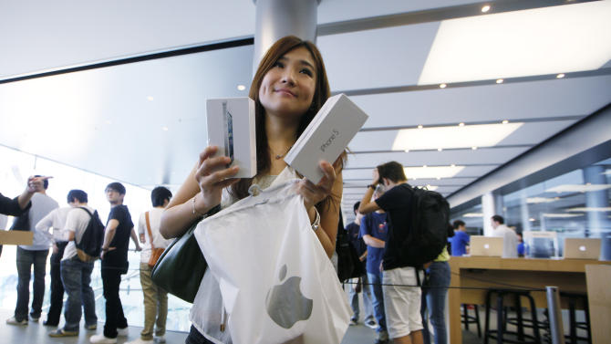 A customer shows her new iPhone 5 at the Apple store in Hong Kong Friday, Sept. 21, 2012. Apple's Asian fans jammed the tech juggernaut's shops in Australia, Hong Kong, Japan and Singapore to pick up the latest version of its iPhone. (AP Photo/Kin Cheung)