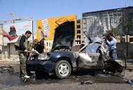 Syrian policemen inspect the site of a car bomb explosion on Mazzeh highway in the capital Damascus