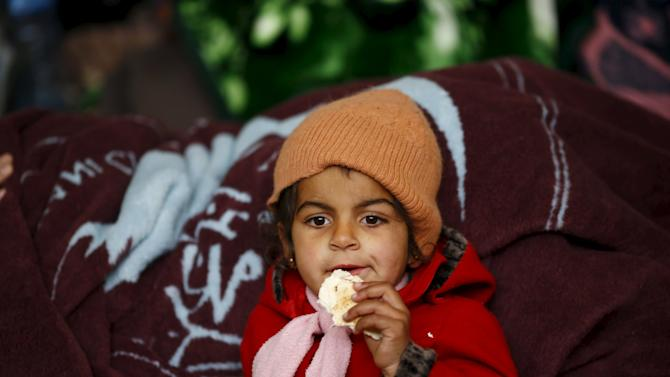 An internally displaced Syrian girl eats at a shelter near the Bab al-Salam crossing, across from Turkey's Kilis province, on the outskirts of the northern border town of Azaz, Syria