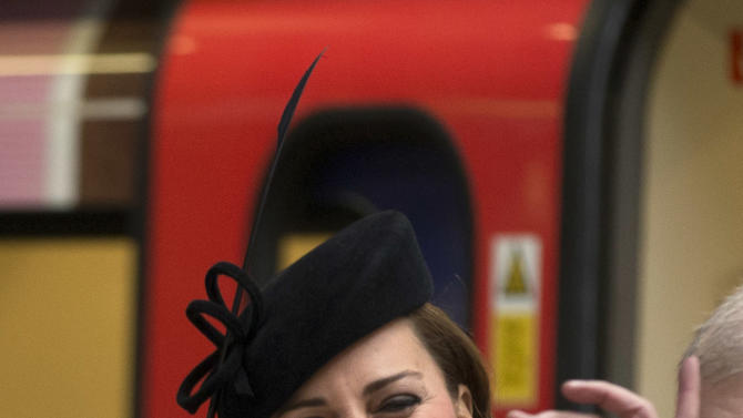 "Britain's Kate, the Duchess of Cambridge, reacts as she is presented a badge that says ""Baby on Board"", normally available to pregnant passengers to encourage others to give them a seat, watched by Britain's Queen Elizabeth II, bottom, at Baker Street underground station in London, for a visit to mark the 150th anniversary of the London Underground, Wednesday, March 20, 2013.  The Queen made her first public engagement in more than a week Wednesday after cancellations following her hospitalization for a stomach bug.  The British head of state joined her husband Prince Philip and their granddaughter-in-law, Kate, for the event marking the 150th anniversary of London's sprawling subway system, affectionately known as the Tube.  (AP Photo/Matt Dunham)"