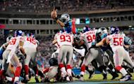 Cam Newton of the Carolina Panthers dives over the New York Giants defense to score a touchdown on September 20, 2012 in Charlotte, North Carolina. The Giants won 36-7