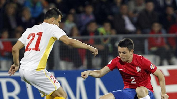 Serbia's Antonio Rukavina, right, challenges for the ball with Macedonia's Mirko Ivanovski during their World Cup 2014 Group A qualifying soccer match at the City Stadium in Jagodina, Serbia, Tuesday, Oct. 15, 2013