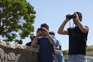 Israelis watch clashes between Syrian troops and rebels near the Golan Heights Quneitra border crossing on June 6, 2013. Syria's army have recaptured the only Golan Heights crossing on the ceasefire line with Israel, in another setback for rebels a day after they were forced out of the strategic town of Qusayr
