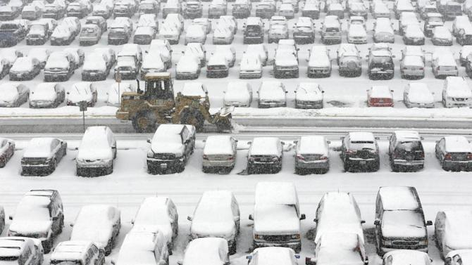 A snow plow clears a parking lot at O'Hare International Airport in Chicago, Tuesday, March 5, 2013. A late winter storm packing up to 10 inches of snow sent officials in weather-hardened Chicago into action Tuesday to prevent a repeat of scenes from two years ago, when hundreds of people in cars and buses were stranded on the city's marquee thoroughfare during a massive blizzard. (AP Photo/Nam Y. Huh)