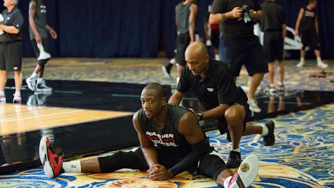 Miami Heat point guard Dwayne Wade stretches during a training camp session at the Atlantis Resort in Paradise Island, Bahamas, Tuesday, Oct. 1, 2013. The two-time defending NBA champions opened training camp Tuesday at the resort, with two practices scheduled for opening day