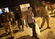 A polling officer carries electronic voting machines (EVM) as he leaves a polling station at the end of polls, during the state assembly election in New Delhi December 4, 2013. REUTERS/Adnan Abidi