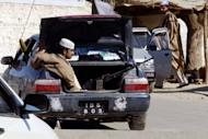 This file photo shows a tribesman sitting with his automatic weapon in the trunk of a car in Pakistan's northwestern tribal belt, near Landi Kotal town, in 2008. A bomb ripped through a market in the area on Saturday, killing at least 11 people and wounding more than 20, according to officials