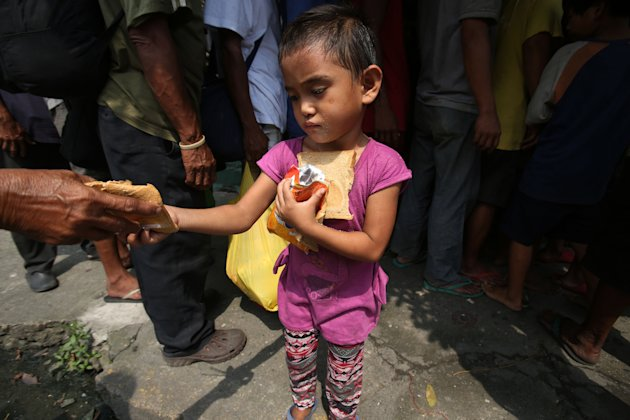 A poor Filipino girl holds bread and drinks she received during a feeding program by Dominican nuns in Manila, Philippines on Wednesday, Sept. 17, 2014. The weekly program gives a free meal to homeless people around the community. (AP Photo/Aaron Favila)