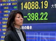 A woman in Tokyo on October 25, 2013 passes an electronic board displaying the Nikkei index level