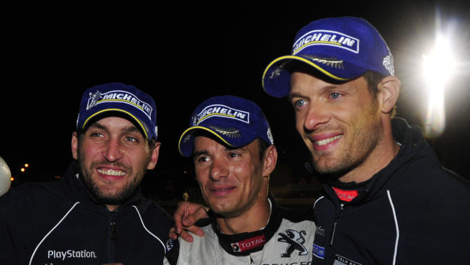 Peugeot drivers, from left, Franck Montagny, of France, Stephane Sarrazin, of France, and Alexander Wurz, of Austria, celebrate after winning the American Le Mans Series' Petit Le Mans auto race at Road Atlanta, Saturday, Oct. 1, 2011, in Braselton, Ga. (AP Photo/Rainier Ehrhardt)
